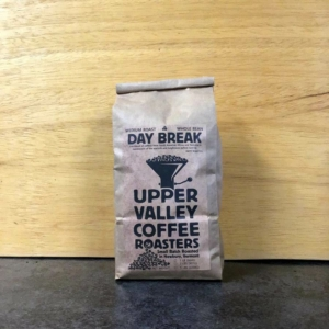 Day Break Blend 1 lb brown bag on a dark surface and light wood background