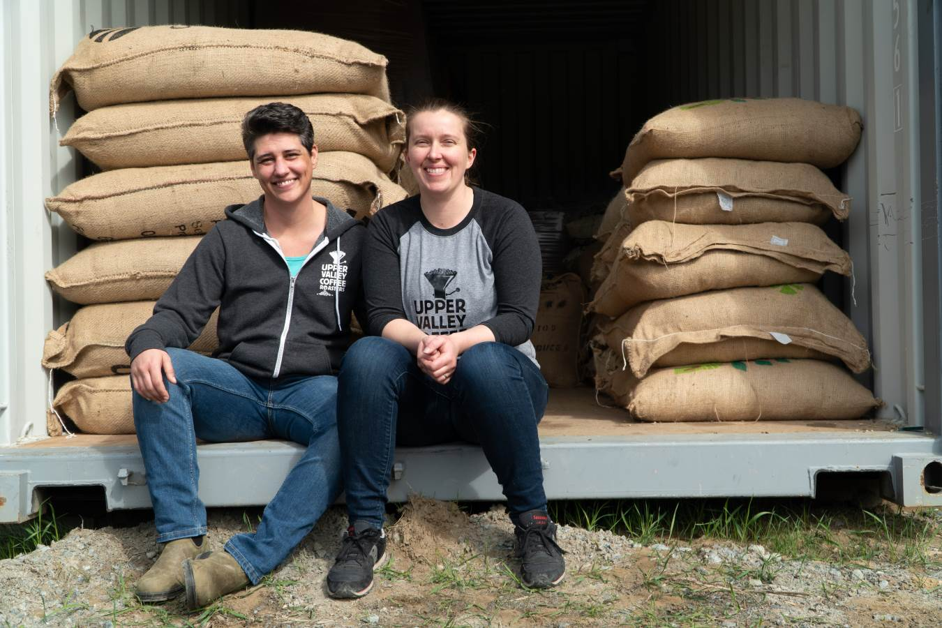 Cal and Andrea sitting in front of stacks of green coffee in burlap bags